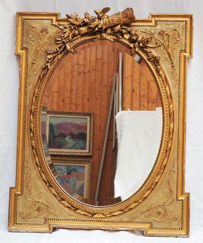 Miroir en bois doré et sculpté à décor de fleurs enserrant un car...