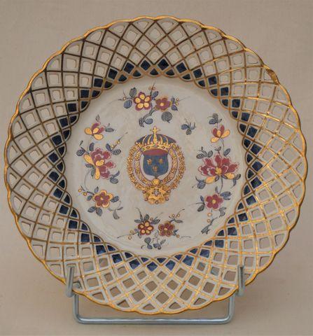Assiette en porcelaine à bords de croisillons ajourés dorés, au c...