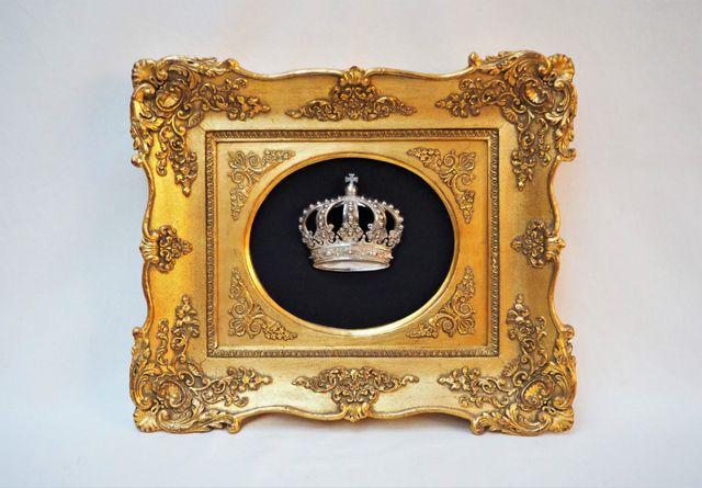 Cadre en bois stuqué doré refermant une couronne royale en bronze...