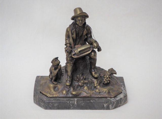Groupe en bronze sculpté représentant un joueur de mandoline acco...