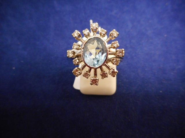 Bague or gris montée d'une pierre bleue entourée de petits diaman...